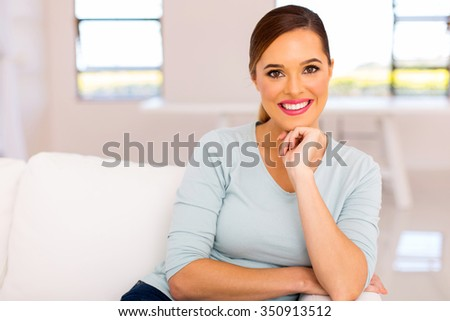pretty young woman sitting on sofa at home - stock photo