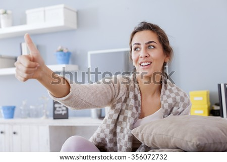 Pretty Young Woman Sitting on the Couch In the Living Room.  - stock photo