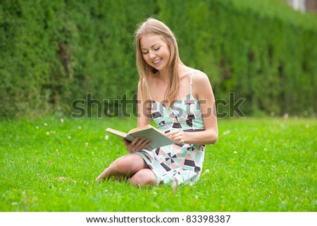 Pretty young woman sitting on the grass and reading book outdoors