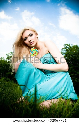 Pretty Young Woman Sitting On The Green Grass