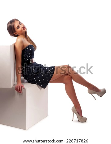 pretty young woman sitting on wooden cubes - stock photo