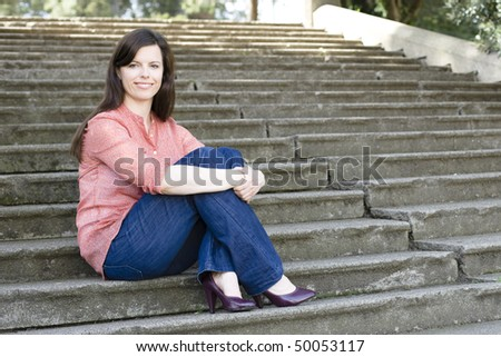 Pretty Young Woman Sitting Outside on Steps With Legs Crossed - stock photo