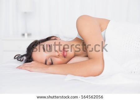 Pretty young woman sleeping with eyes closed in a bright bedroom at home