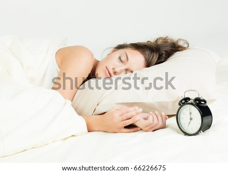 Pretty young woman sleeps in her bed - stock photo