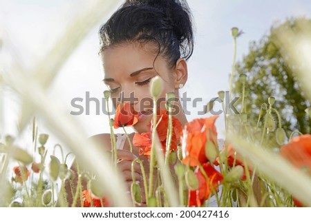 pretty young  woman smelling a poppy - stock photo