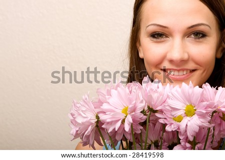 Pretty young woman smelling daisies