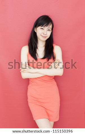 pretty young woman smiling against red background - stock photo