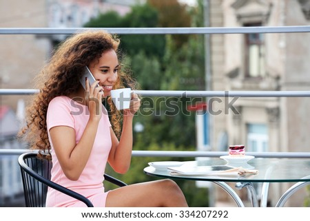 Pretty young woman speaking by cellphone and drinking coffee at summer terrace - stock photo