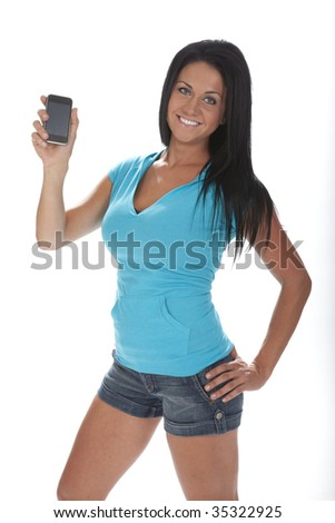 Pretty young woman standing holding cell phone. White background.