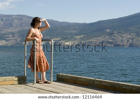 Pretty young woman standing on pier looking into the distance, wearing summer dress. Lake and mountains in background.