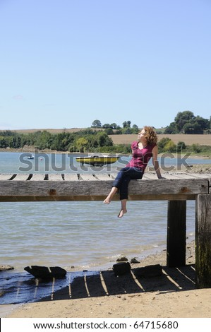 Pretty young woman sunbathing on landing stage in brittany, france - stock photo