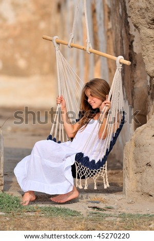 pretty young woman swinging outdoor in summer - stock photo