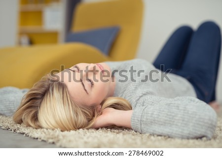 Pretty young woman taking a nap lying on her back on a carpet with her hands clasped being her head and her eyes closed as she relaxes - stock photo