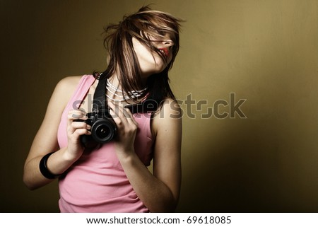 Pretty  young  woman taking a photo with a digital camera - stock photo