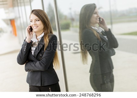 Pretty young woman talking on the phone in front of office - stock photo