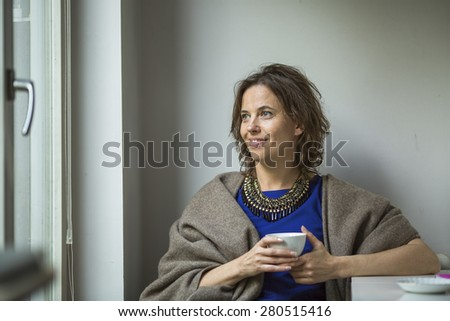Pretty young woman thoughtfully with a Cup of tea near the window.
