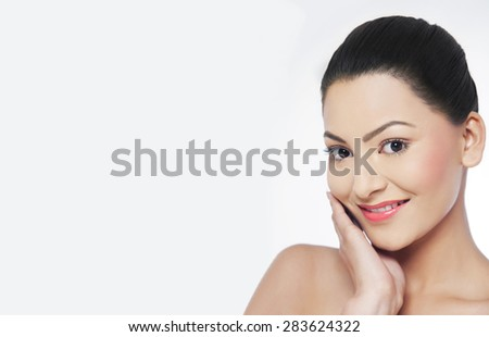 Pretty young woman touching her face - stock photo