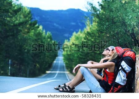 Pretty young woman tourist hitchhiking along a road. - stock photo