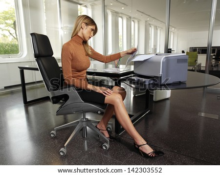 pretty young woman using a copy machine - stock photo