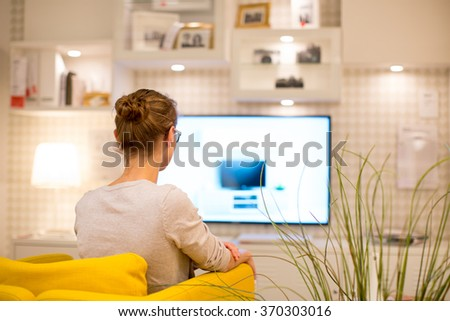 Pretty, young woman watching TV at home (color toned image; shallow DOF) - stock photo