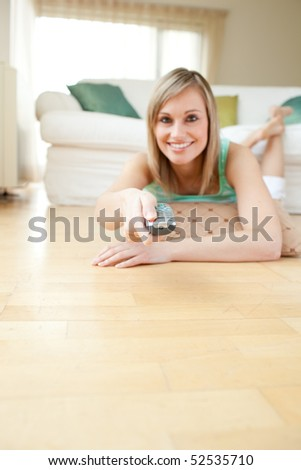 Pretty young woman watching TV lying on the floor at home - stock photo