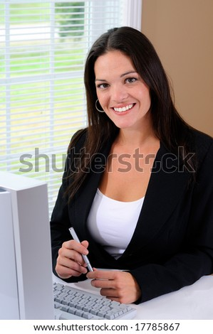 Pretty Young Woman Wearing A Business Suit Working In An Office With A Computer