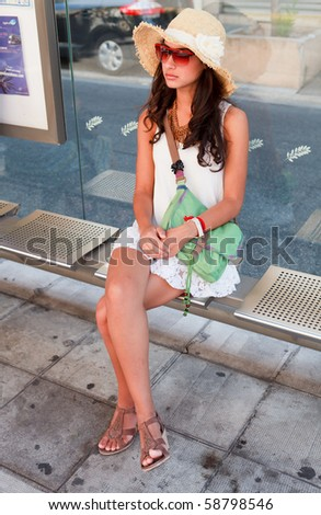 Pretty young woman wearing a hat waiting for a bus to arrive in Nice, France. - stock photo