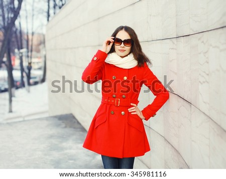 Pretty young woman wearing a red coat, sunglasses and scarf in city - stock photo