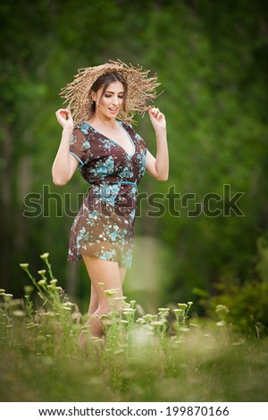 Pretty young woman wearing a straw hat posing in forest. Very attractive brunette girl with short dress, outdoor shot. Romantic female in the field during shiny day. - stock photo