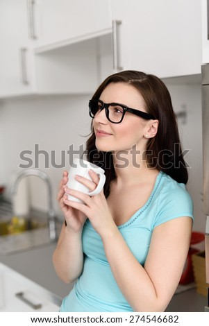 Pretty young woman wearing glasses enjoying coffee in her kitchen cradling the mug in her hands as she stares dreamily into the air - stock photo