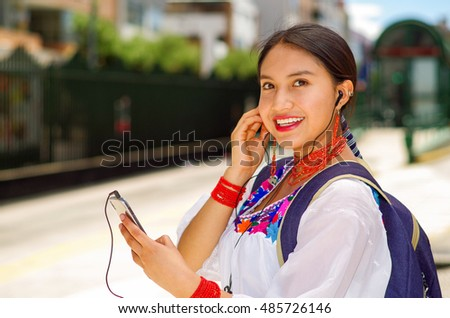 Pretty young woman wearing traditional andean blouse and blue backpack, waiting for bus at outdoors station platform, using mobile phone listening to music with headphones connected, smiling happily