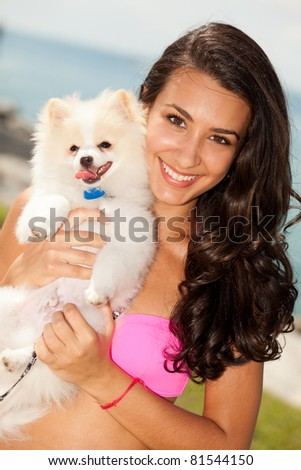 Pretty young woman with a pomeranian puppy at the beach. - stock photo