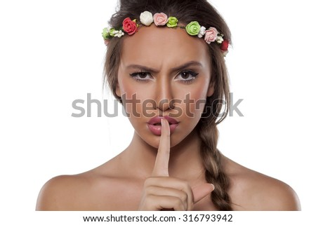 pretty young woman with a wreath of flowers and braid make a silent gesture - stock photo