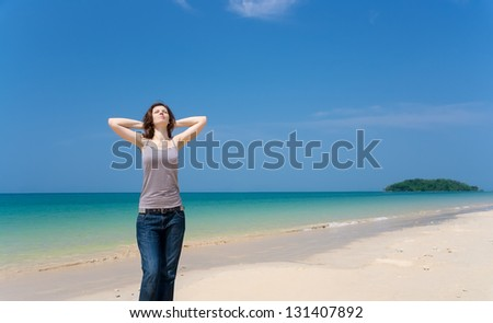 Pretty young woman with arms raised and eyes shut standing on the tropical beach relaxed. Expressing positivity - stock photo