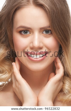 Pretty young woman with beautiful make-up and perfect healthy skin touching her face - stock photo