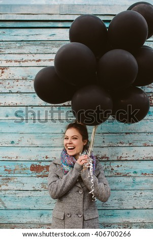 Pretty young woman with black balloons on vintage wooden background  - stock photo