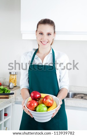 Pretty young woman with bowl of apples and bananas in kitchen