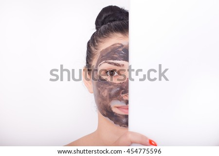 Pretty young woman with facial mask behind white board isolated on white background. Half face. Space for your text