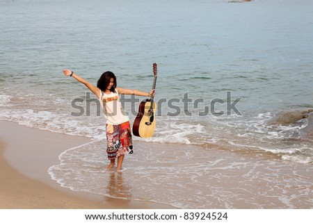 Pretty young woman with guitar on beach