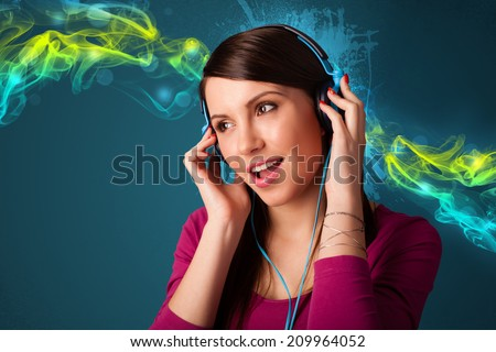 Pretty young woman with headphones listening to music, glowing smoke concept - stock photo
