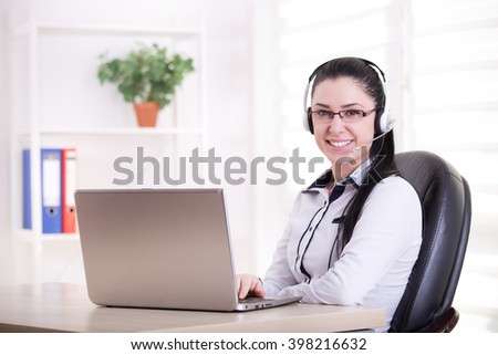 Pretty young woman with headset working as operator on laptop in the office. Looking at camera and smiling - stock photo