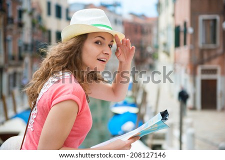 Pretty young woman with map in Venice - stock photo