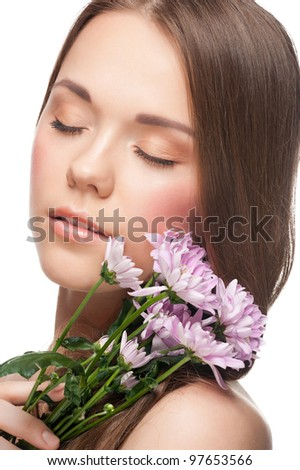 Pretty young woman with perfect healthy skin and fresh makeup with flowers in her hands
