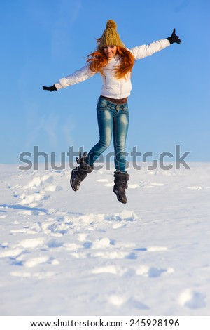 Pretty young woman with red hair take a fun on the snow field - stock photo