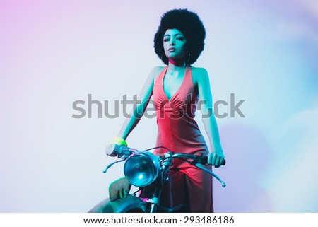 Pretty Young Woman with Short Curly Hair, Looking at the Camera While Posing on her Motorcycle Against White Background. - stock photo
