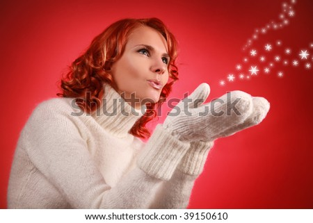 pretty young woman with snow flakes on red background - stock photo