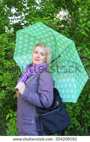 pretty young woman with the big green umbrella outdoors - stock photo