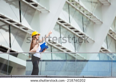 Pretty young woman working as architect on a construction site