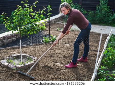 pretty young woman working in garden - stock photo