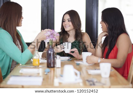 Pretty young women chatting and having coffee at a restaurant
